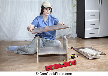 One Caucasian Woman Putting Together Self Assembly Furniture On Floor.