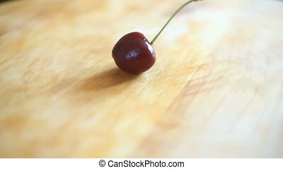 One cherry lies on a wooden board that rotates around its axis