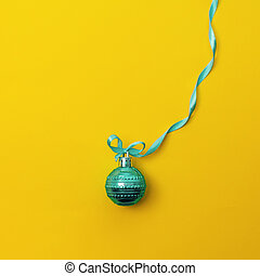 One christmas ball on yellow background