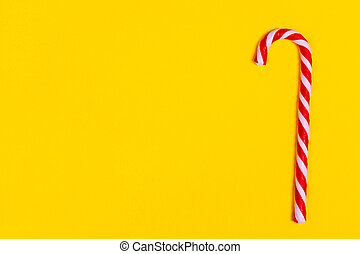 one christmas candy cane on yellow backgroud, copy space.