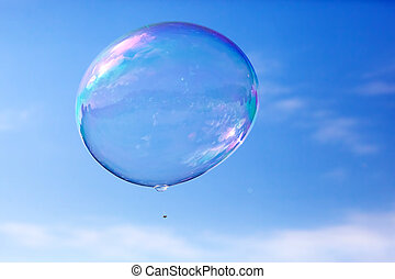 One clean soap bubble flying in the air, blue sky.