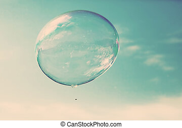 One clean soap bubble flying in the air, blue sky. Vintage