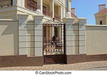 brown metal door with a forged pattern on a concrete fence in the street