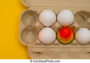 one colored egg in a package with ordinary white eggs. the concept of LGBT