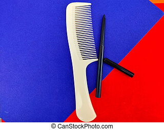 One comb and kajal pencil isolated on red and blue background