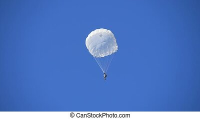 One courageous paratrooper flying on white round parachutes ...