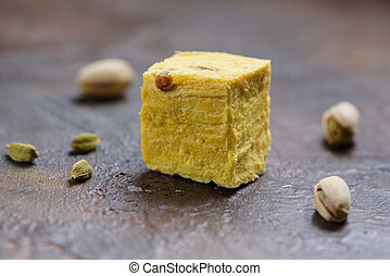 One cube of dessert soan papdi, cardamom grains and pistachios on concrete kitchen surface.