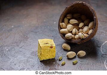 One cube of dessert soan papdi, cardamom grains and pistachios on concrete kitchen worktop..