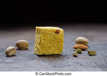 One cube of dessert soan papdi, cardamom grains, pistachios and almond on a concrete kitchen surface.