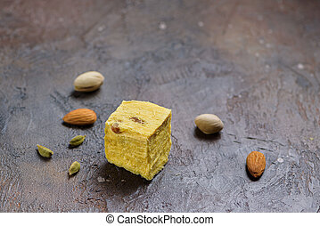 One cube of dessert soan papdi, cardamom grains, pistachios and almond on concrete kitchen surface.