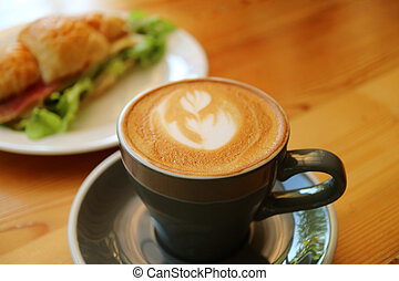 One Cup of Hot Cappuccino Coffee in a Dark Grey Cup Served on Wooden Table with Blurry Croissant Sandwich in Background