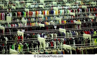 One customer walk among clothes in shop department - One...