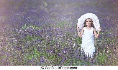 One cute girl running at camera through the field. Child is in a white dress