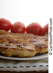 one cutlet with organic tomato on a plate