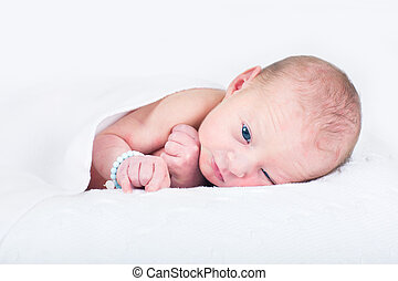 One day old newborn baby relaxing on a knitted white blanket