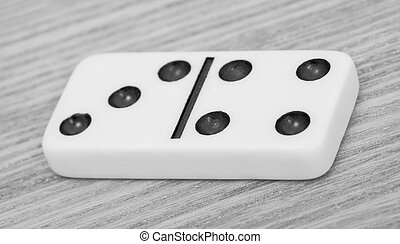 One dominoes lies on wooden surface close up