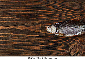 One dried or jerky salted roach, tasty clipfish on wooden ...