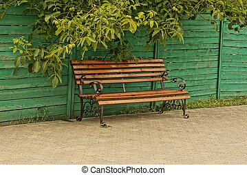 one empty brown wooden bench stands on a gray sidewalk