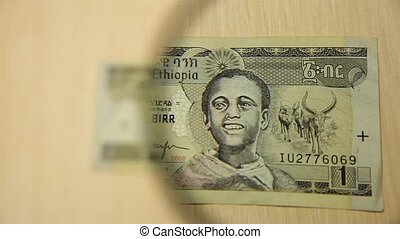 View a One Ethiopian Birr bill lying on a table with a magnifying glass. concept of business and finance.