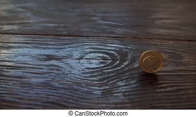 One Euro coin spinning in slow motion on wooden background
