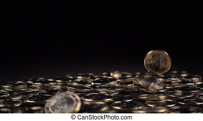 one euro coins fall on a black background