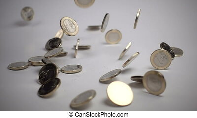 one euro coins fall on a white background