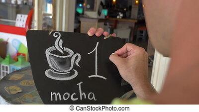 One euro for tasty aromatic coffee - Man writing one euro...