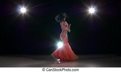 One european woman belly dancer dancing on black, back light, slow motion