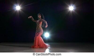 One european woman belly dancer starting dancing on black, back light, slow motion