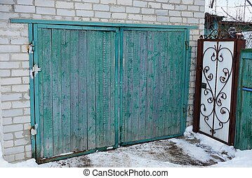 facade of a gray brick garage with a green wooden gate outside in the snow