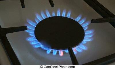 One gas burners burn blue flame on a gas stove