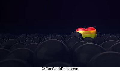 One gay, pride, rainbow heart colour balloon is flying through other balloons. Dark purple background. Ideal title text background. Concept of contrasting the LGBT lesbian gay bisexual transexual community with society.