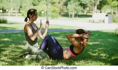 One girl doing abs exercises in the park, other girl helping...