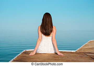 One girl in a white dress sitting on the pier and looking into the distance