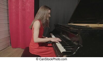 One girl playing on piano in red dress