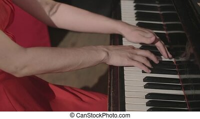 One girl playing on the piano in red dress