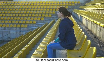 One girl sits in the grandstand of the stadium and is a fan of the game, 4k