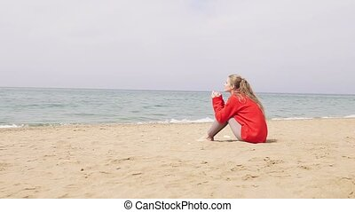 one girl sits on a sandy beach and looking at the sea