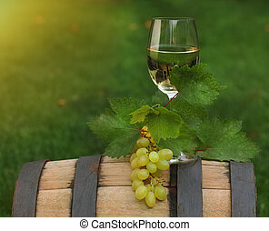 One glass of white wine on the wine barrel - One glass of...