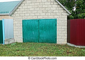 one gray brick garage with closed glazed green gates on the street in the grass