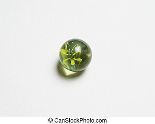 One green glass ball with caustic on a white background