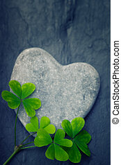 One grey heart shaped rock with four shamrocks on a tile backrgo