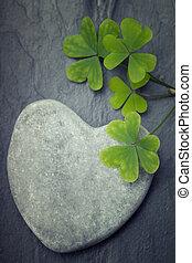One grey heart shaped rock with shamrocks on a beautiful tile b