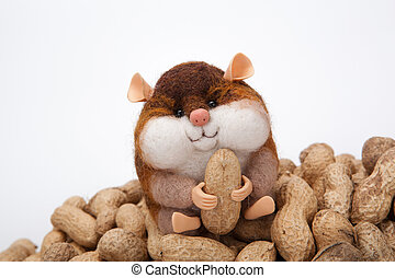 handmade artificial chipmunk with peanuts on a bunch of nuts on a white background