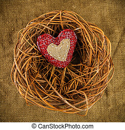 One handmade heart in the nest on sackcloth background