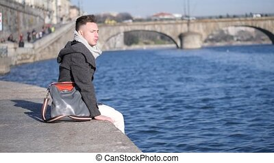 One handsome young man in urban setting in European city, Turin in Italy by the river Po, in cold winter day
