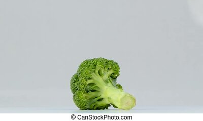 one head of broccoli spinning on white background - rotating...