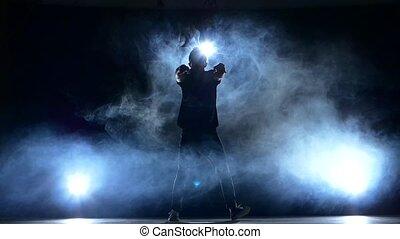 One hip hop break-dancer stylish man dancing, smoke, silhouette, slow motion