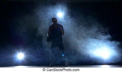 One hip hop break-dancer stylish man in sunglasses continue dancing, smoke, silhouette, slow motion