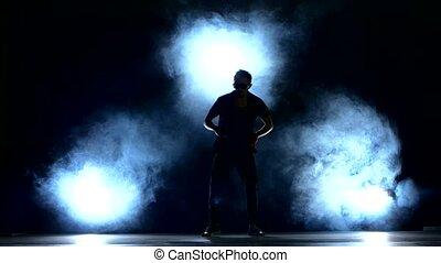 One hip hop break-dancer stylish man in sunglasses dancing, smoke, silhouette